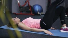 Kvinnan i rosa färger som gör abs, övar i en idrottshall lager videofilmer