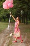 Kvinnan i rosa färgklänning med rosa färgballonger och den vide- korgen i gröna söndag parkerar royaltyfria bilder