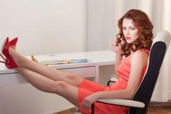 Kvinnan i rosa färgklänning sitter på ett skrivbord med hans fot upp på skrivbordet Arkivbild