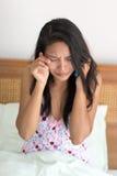 Kvinnan i säng kallar hennes telefon Royaltyfri Fotografi