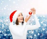 Kvinnan i santa hjälpredahatt med jul klumpa ihop sig Royaltyfria Bilder