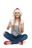 Kvinnan i Santas hattsammanträde däckar på visningtumen undertecknar upp Arkivbilder