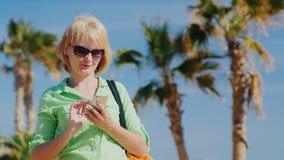 Kvinnan i sommar beklär maskinskrivning på din telefon arkivfilmer