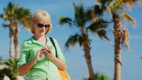 Kvinnan i sommar beklär maskinskrivning på din telefon lager videofilmer