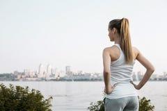 Kvinnan i sport beklär anseende på stadsbackbrounden royaltyfri foto