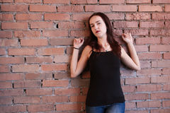 Kvinnan i svartöverkant poserar nära en tegelstenvägg Arkivbild