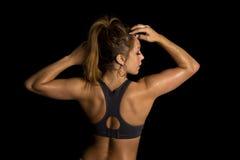 Kvinnan i svart sportbehåbaksida räcker upp royaltyfri bild