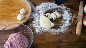 Kvinnan i svarta handskar gör små bollar från degen för att laga mat pajen med kött arkivfilmer