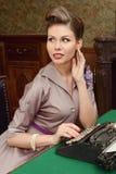 Kvinnan i tappninginre skrivar ut på en gammal skrivmaskin Royaltyfri Fotografi