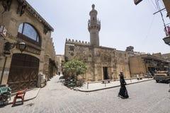Kvinnan i traditionella muslim klär korsa en tom gata i den gamla Kairo, Egypten arkivbilder