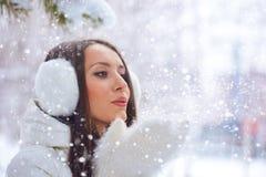 Kvinnan i vinter parkerar att blåsa på snow Arkivbilder