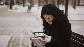 Kvinnan i vinter parkerar den talande mobiltelefonen, sms stock video