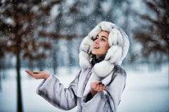 Kvinnan i vinter parkerar har gyckel med en snow Fotografering för Bildbyråer