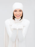 Kvinnan i vinterkläder med något gömma i handflatan på Arkivfoto