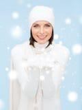 Kvinnan i vinterkläder med något gömma i handflatan på Arkivfoton