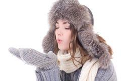 Kvinnan i vinterkläder som blåser något från henne, gömma i handflatan isolaten Arkivfoton