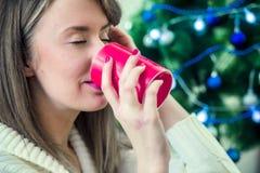 Kvinnan i vinterkläder som tycker om varma ögon för en drink, stängde sig Portra Royaltyfri Bild