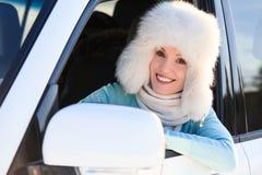Kvinnan i vit pälsfodrar hatten i en bil Royaltyfri Bild