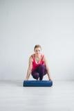 Kvinnan i vitt rum fördelar en matt yoga Royaltyfri Bild