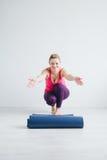 Kvinnan i vitt rum fördelar en matt yoga Royaltyfri Foto