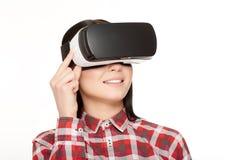 Kvinnan i VR-hörlurar med mikrofonpress knäppas och den hållande ögonen på videoen Arkivbild
