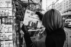 Kvinnan inhandlar en New York Times med den Obama och trumftidningen Royaltyfri Bild