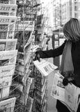Kvinnan inhandlar en tidning för Le Mondefranskapress från en newssta royaltyfri bild