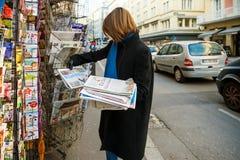 Kvinnan inhandlar tidningen för Het Laastste Nieuws från en tidningskiosk Arkivbilder