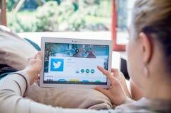 Kvinnan installerar den Twitter applikationen på den Lenovo minnestavlan Arkivfoton