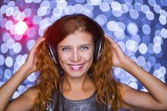 Kvinnan isten till musik i hörlurar på ljus bollbokehbackgroun arkivbilder