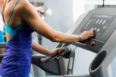 Kvinnan justerar treadmillen Royaltyfri Foto