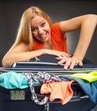 Kvinnan kämpar för att stänga en full resväska royaltyfri foto