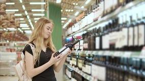 Kvinnan köper alkohol för hem lager videofilmer