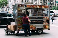 Kvinnan köper mat på matlastbilen i New York arkivbilder
