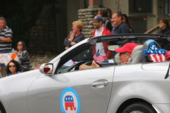 Kvinnan kör i 4th Juli ståtar i bil med republikanska partietlogo Arkivfoto