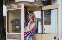 Kvinnan kallar genom att använda den gamla telefonen Royaltyfri Fotografi