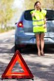 Kvinnan kallar till en service som plattforer vid en vit bil Arkivbild