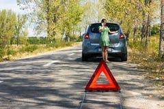 Kvinnan kallar till en service som plattforer vid en vit bil Arkivfoton