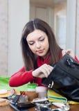 Kvinnan kan inte finna något i henne handväskan Royaltyfri Foto