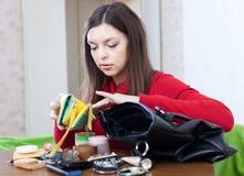 Kvinnan kan inte finna något i hennes handväska Arkivbild
