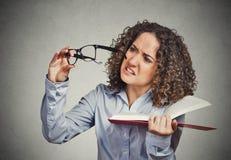 Kvinnan kan inte se att den lästa boken har exponeringsglas för visionproblem fel Royaltyfri Bild