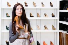 Kvinnan kan inte välja stilfulla pumpar Royaltyfri Fotografi