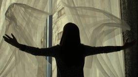 Kvinnan kastar hänger upp gardiner ut stock video