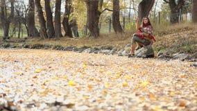 Kvinnan kastar stenar in i vattnet arkivfilmer