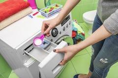 Kvinnan kastar tvätteritvättmedel in i tvagningmaskinen royaltyfri foto