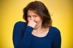 Kvinnan klämmer hennes näsa, dålig lukt royaltyfri fotografi