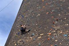 Kvinnan klättrar ett konstgjort vaggar upp väggen - som säkras med rep ag royaltyfria foton
