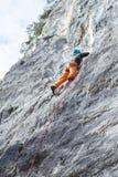 Kvinnan klättrar på en stenvägg Arkivbild