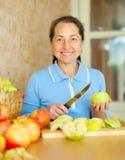 Kvinnan klipper äpplen för äppledriftstopp Arkivfoto