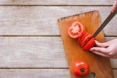 Kvinnan klipper den röda tomaten på delar på träskrivbordet Royaltyfria Foton